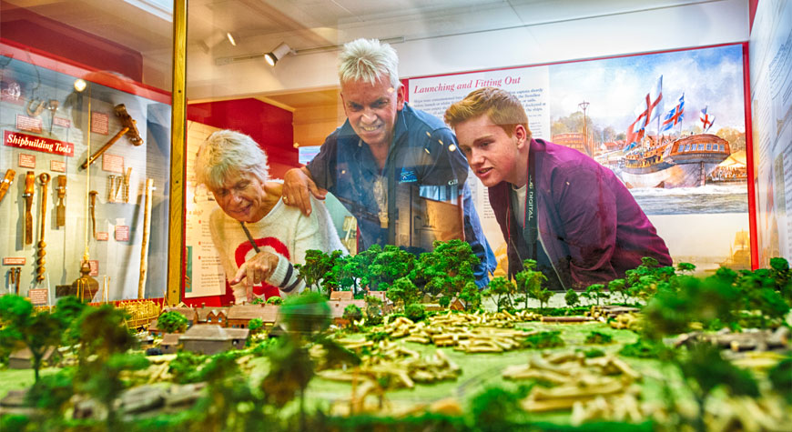 A family examine the model of Buckler's Hard village in the Maritime Museum