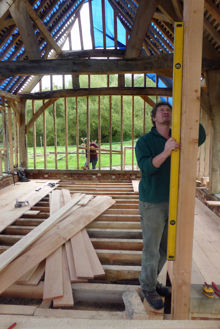 Worker uses a spirit level to check a section of timber