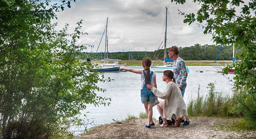 A family watch the boats on Beaulieu River from the Woodland Walk