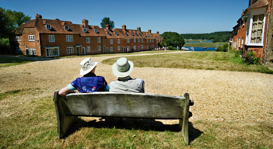 Two visitors sit on a bench at the top of Buckler's Hard high street